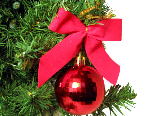 Red bow and round ornament hanging from Christmas Tree