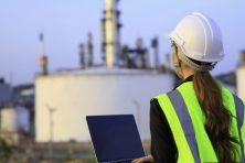 Female engineer foreman wearing safety helmet using laptop working in oil refinery industry plant background.